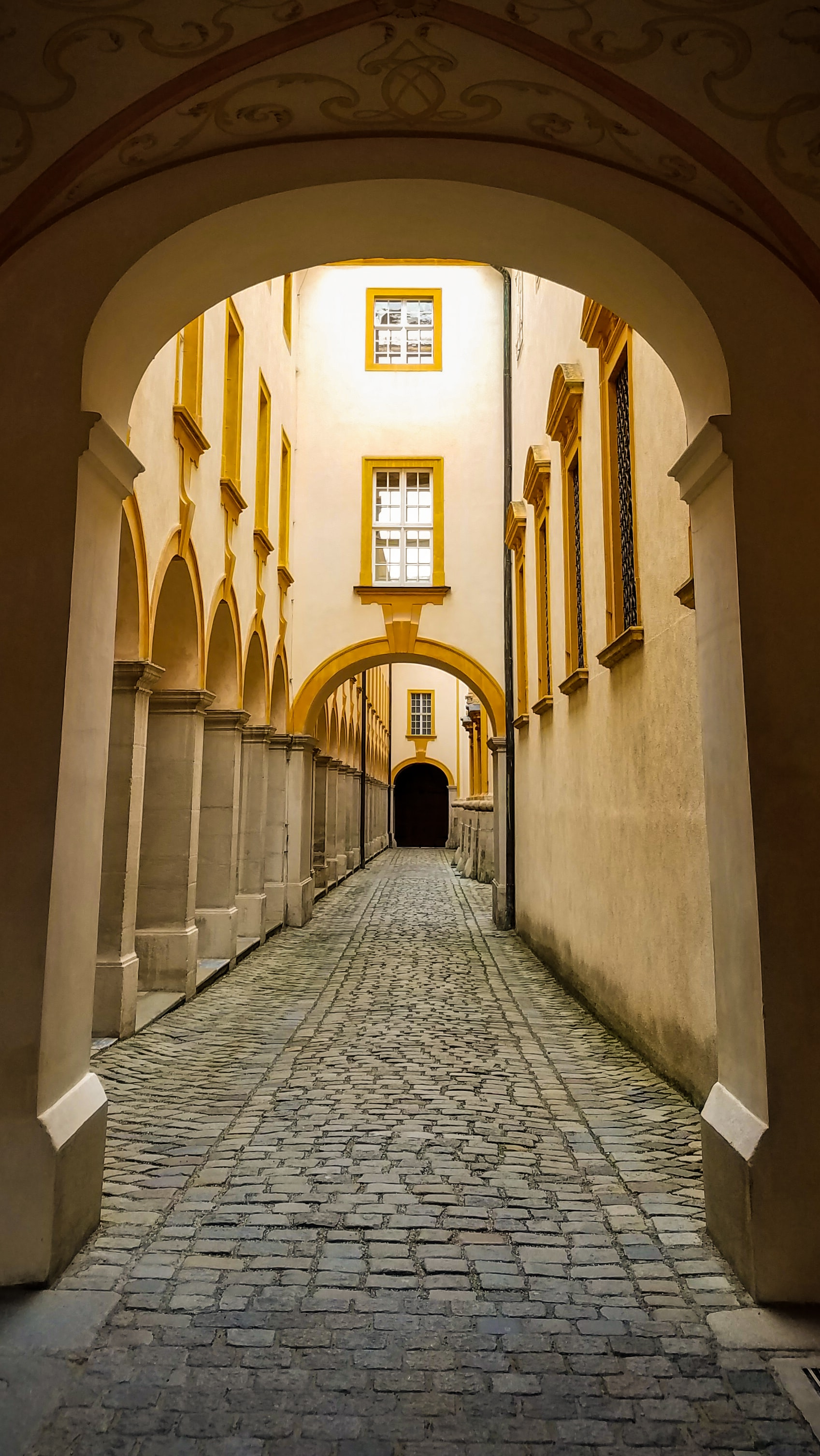 A view down a street whose space is created by a series of arches