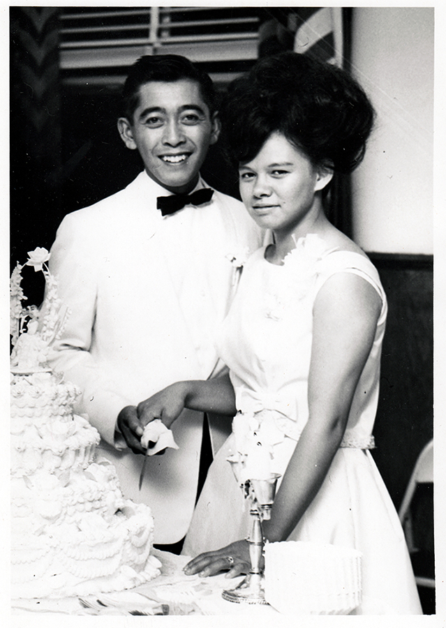 Black and white photograph of Ronald and Violeta Edar at their wedding reception, posed in front of a wedding cake