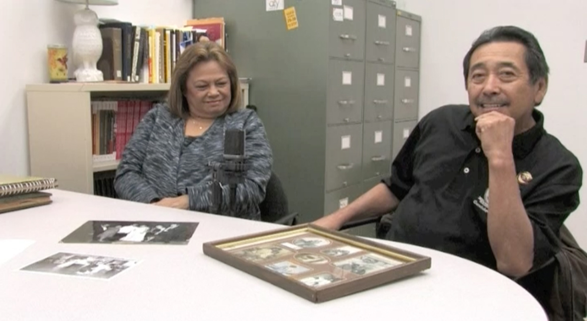 Ronald and Violeta Edar sitting at a table with picture frames in front of them
